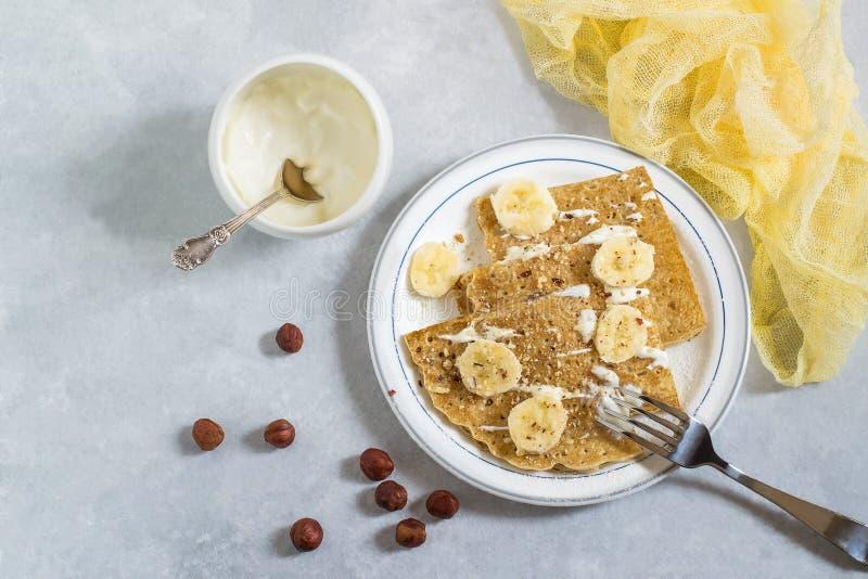 Amincissez les crêpes russes avec la crème sure, les bananes et les noisettes photo stock