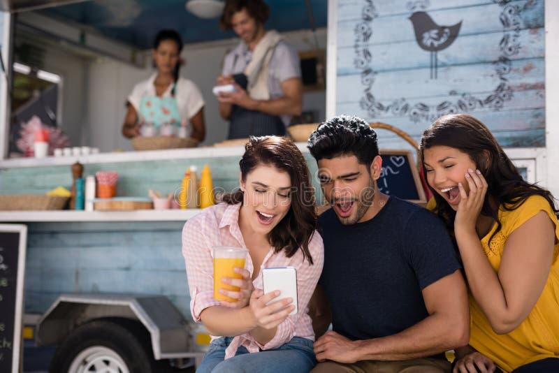 Amis à l'aide du téléphone portable au fourgon de camion de nourriture image libre de droits