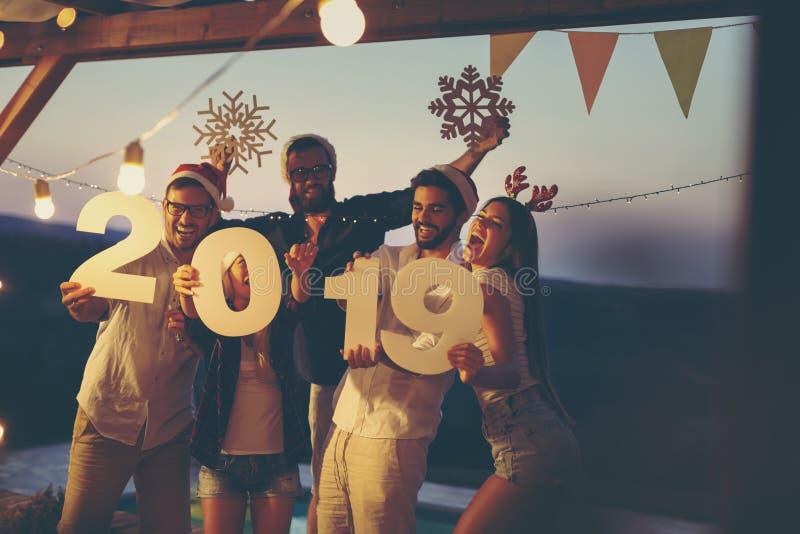 Amis à la réception au bord de la piscine extérieure de réveillon de la Saint Sylvestre images stock