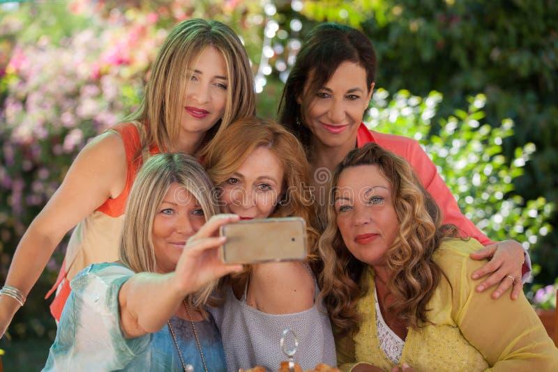 Amis âgés par milieu faisant la photo de selfie images stock