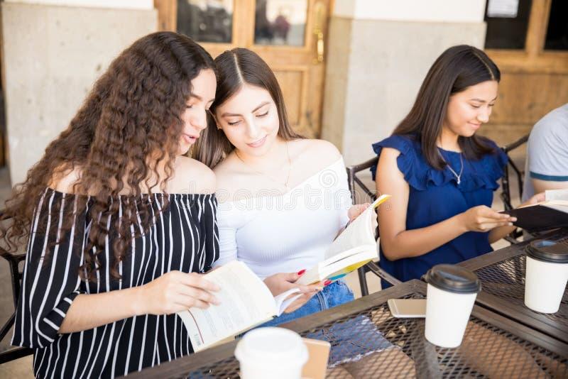 Amis adolescents appréciant des livres de lecture au café photo stock