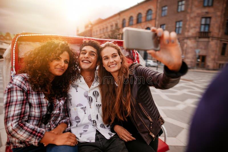 Amis adolescents prenant le selfie sur le tricycle photos stock
