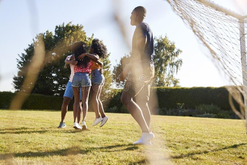 Amis adultes dans un petit groupe de célébration sur le terrain de football photo stock