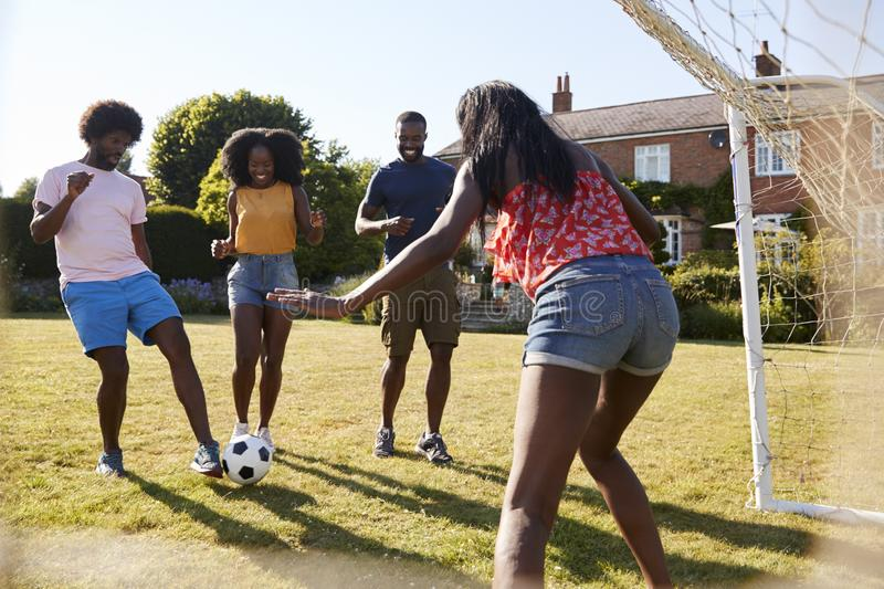 Amis adultes noirs ayant un jeu fun du football dans le jardin photographie stock