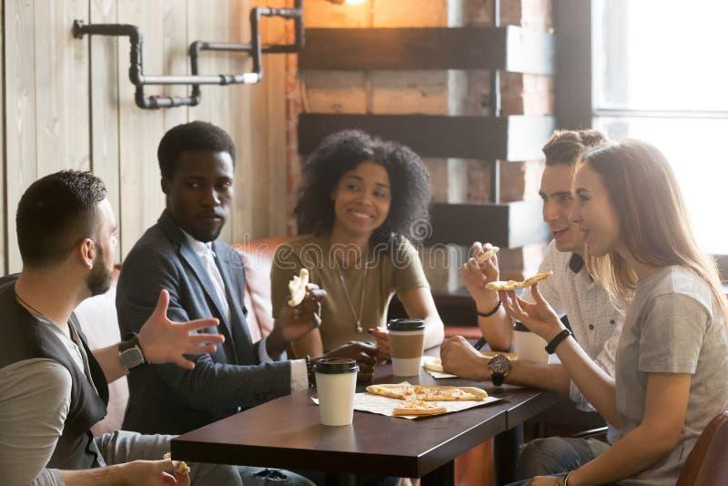 Amis africains et caucasiens multi-ethniques parlant mangeant de la pizza images libres de droits