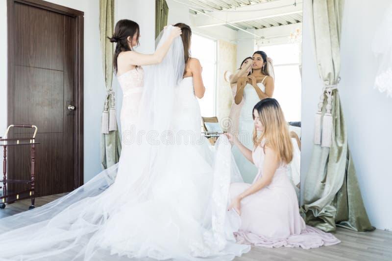 Amis aidant la jeune mariée avec épouser des préparations images stock