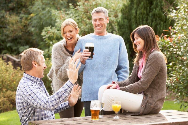 Amis appréciant à l'extérieur la boisson dans le jardin de Pub image stock