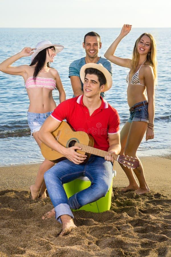 Amis appréciant à la plage avec la guitare photo stock