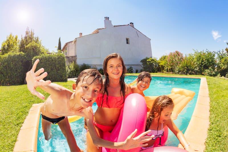 Amis appréciant la réception au bord de la piscine extérieure en été photo libre de droits