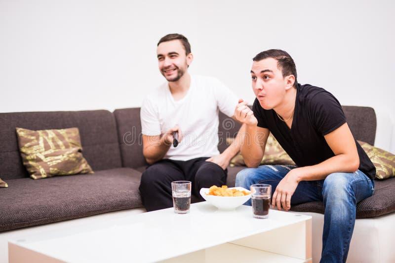 Amis appréciant le football dans la TV avec des boissons et des casse-croûte sur le sofa photos libres de droits