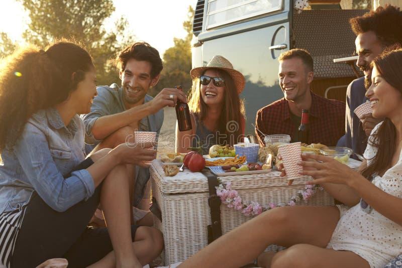 Amis appréciant un pique-nique près de leur camping-car photographie stock libre de droits