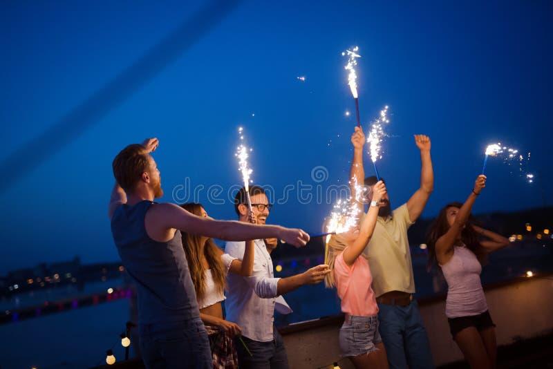 Amis appr?ciant une partie de dessus de toit et dansant avec des cierges magiques image stock