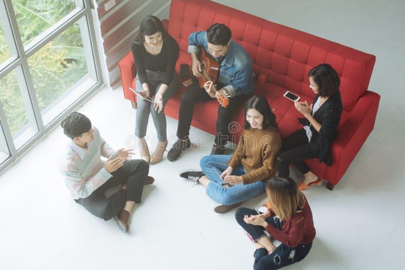 Amis asiatiques heureux d'adolescent appréciant chanter et jouer la guitare à la maison photographie stock libre de droits
