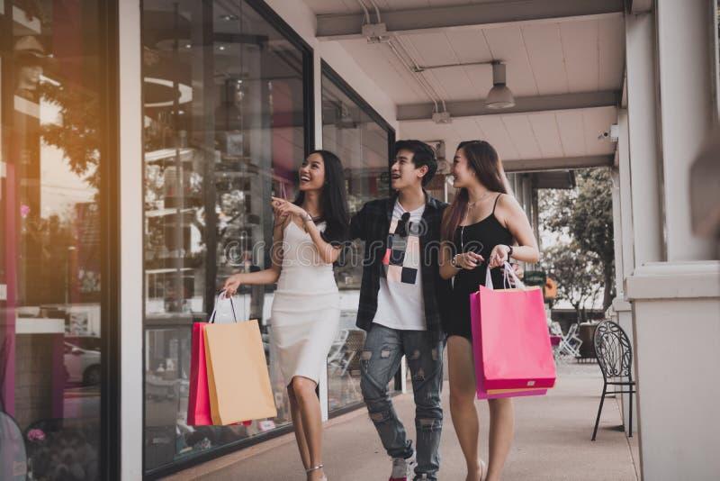 Amis asiatiques passant le temps ensemble et marchant sur le mail avec des paniers photo stock