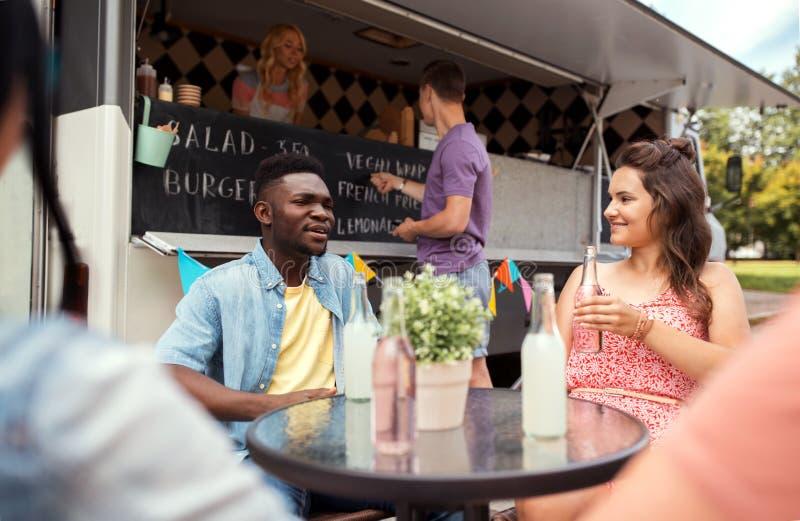 Amis avec des boissons se reposant à la table au camion de nourriture photos libres de droits