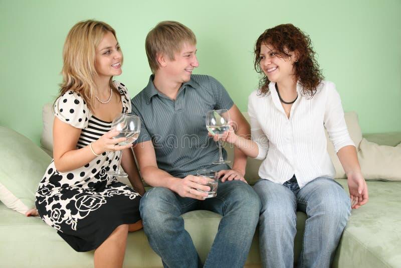 Amis avec des glaces sur le sofa photographie stock