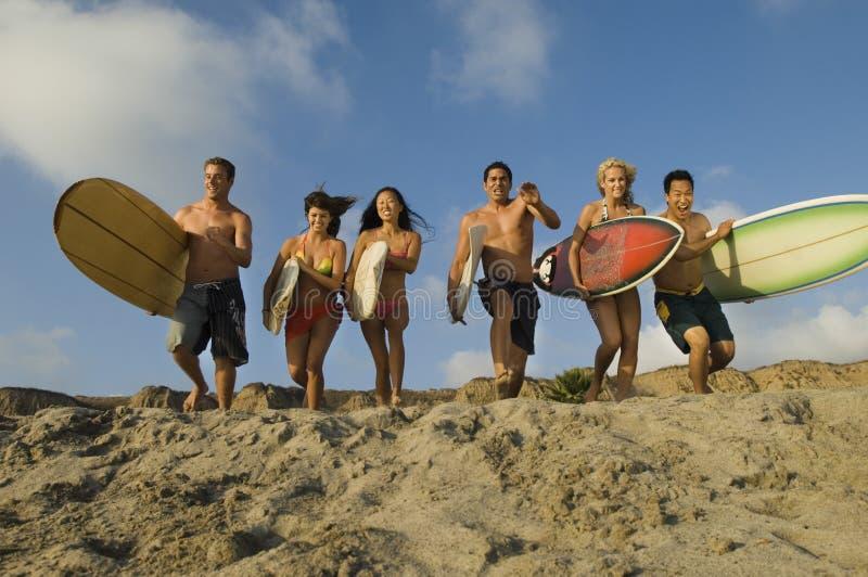 Amis avec des planches de surf fonctionnant sur Sandy Beach photo libre de droits