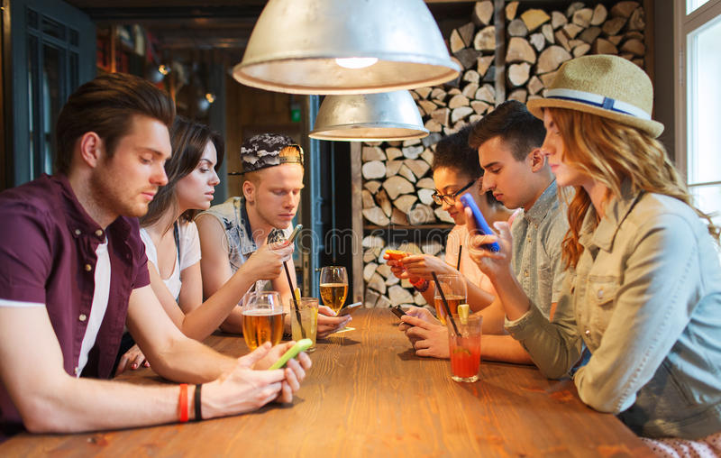 Amis avec des smartphones et boissons à la barre photos stock