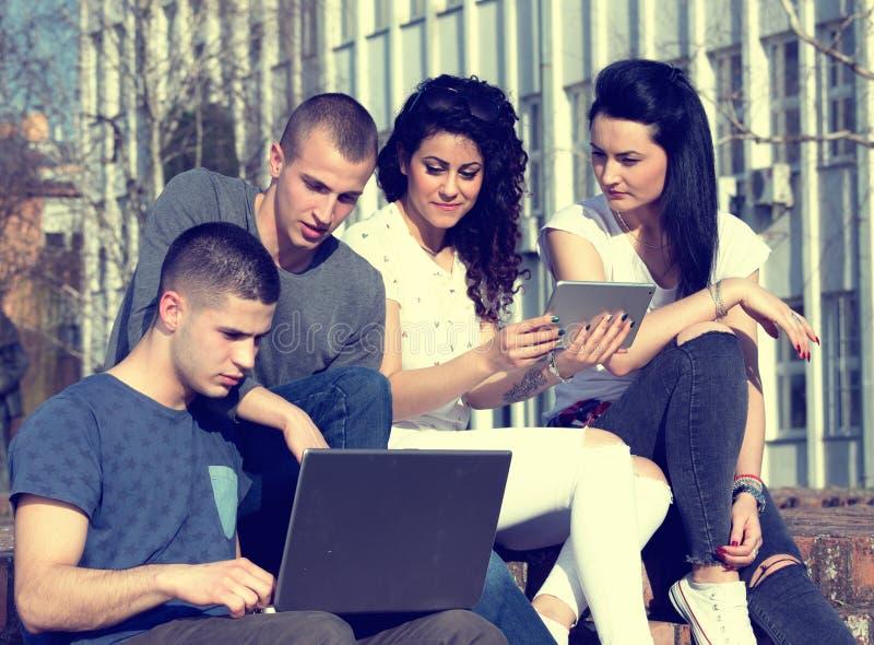 Amis avec l'ordinateur portable sur le banc images stock