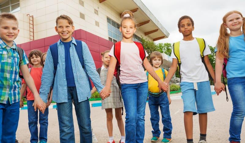 Amis avec la promenade de sacs à dos près du bâtiment scolaire photographie stock