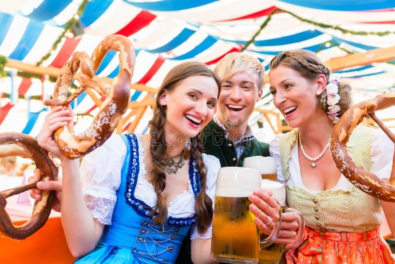 Amis avec les bretzels géants dans la tente bavaroise de bière photos libres de droits