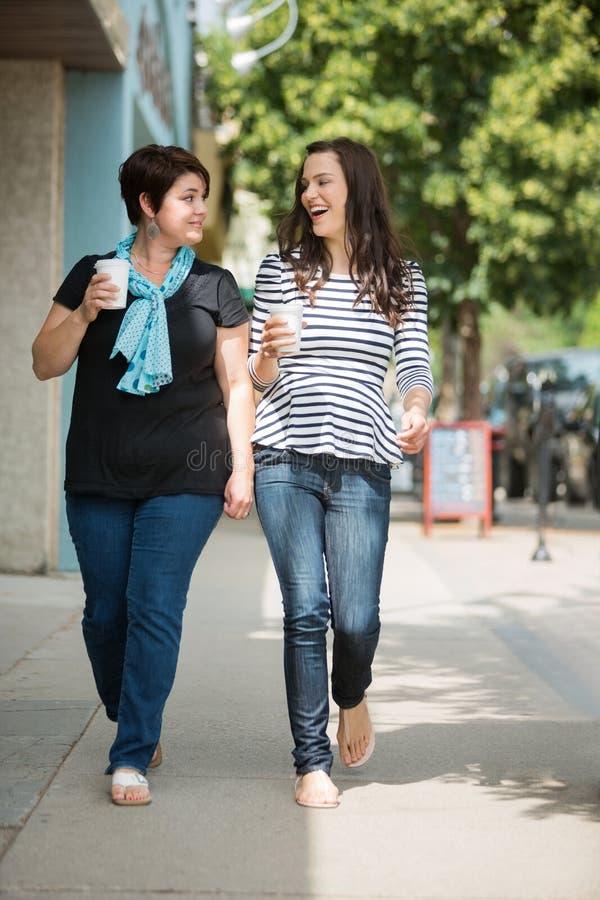 Amis avec les tasses de café jetables marchant dessus photos stock