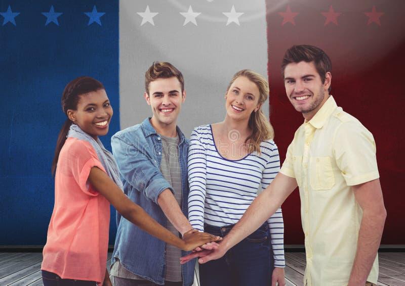 Amis avec leurs mains empilées contre le drapeau français à l'arrière-plan image stock