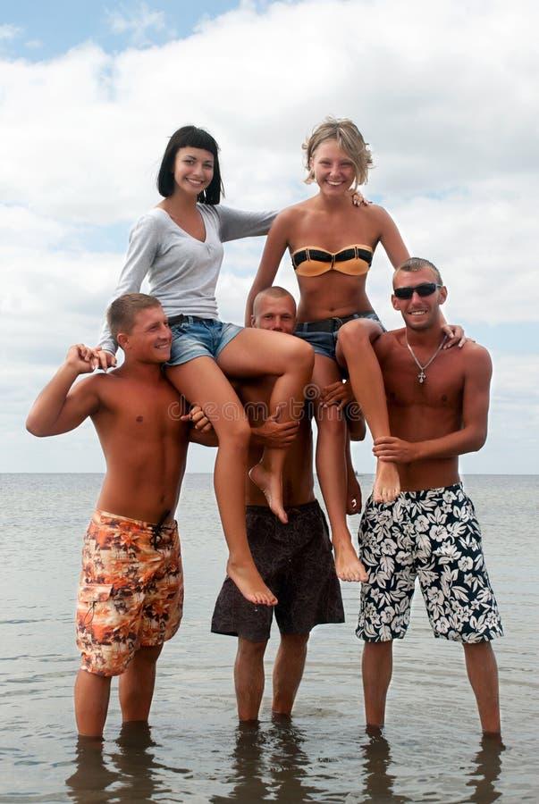 Amis ayant l'amusement à la plage photographie stock
