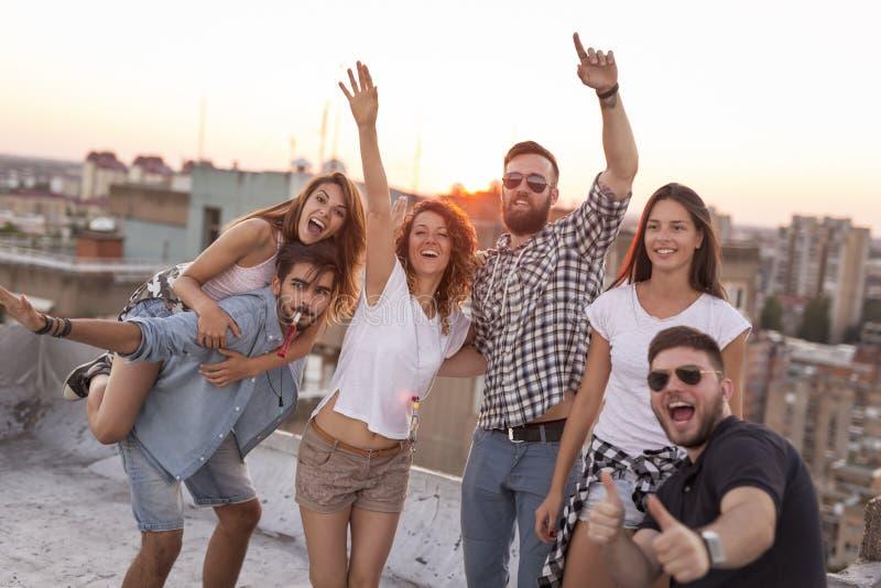 Amis ayant l'amusement à une partie de dessus de toit photos libres de droits