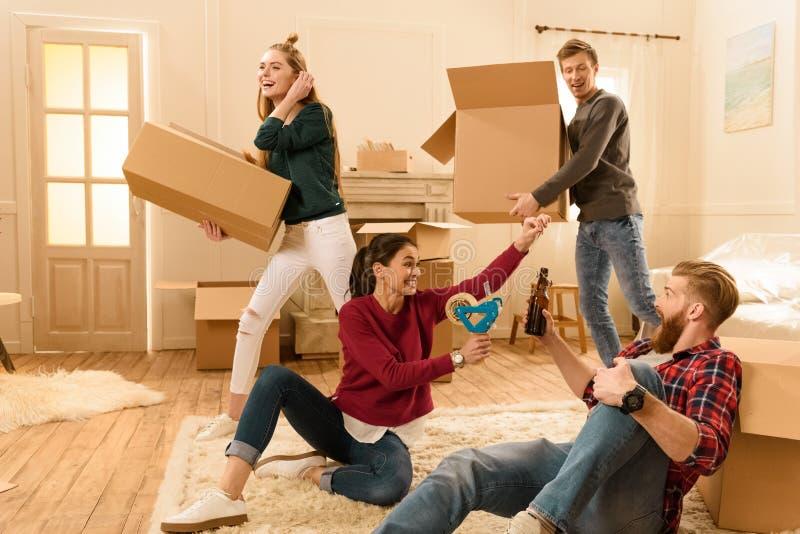 Amis ayant l'amusement dans la nouvelle maison tout en déballant des choses image libre de droits