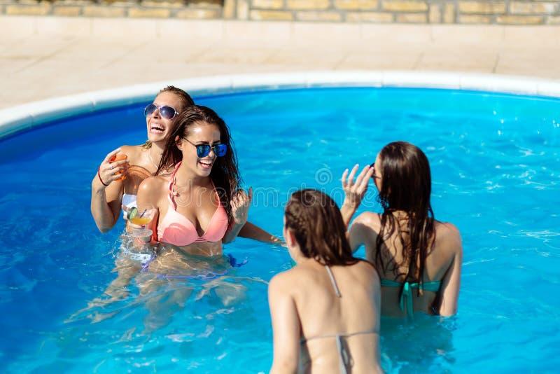 Amis ayant l'amusement dans la piscine image stock