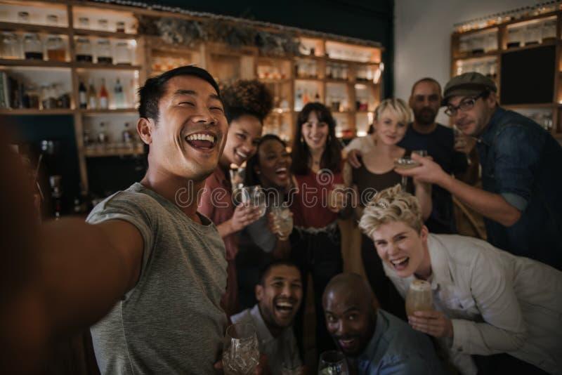 Amis ayant l'amusement et prenant des selfies dans une barre photos libres de droits