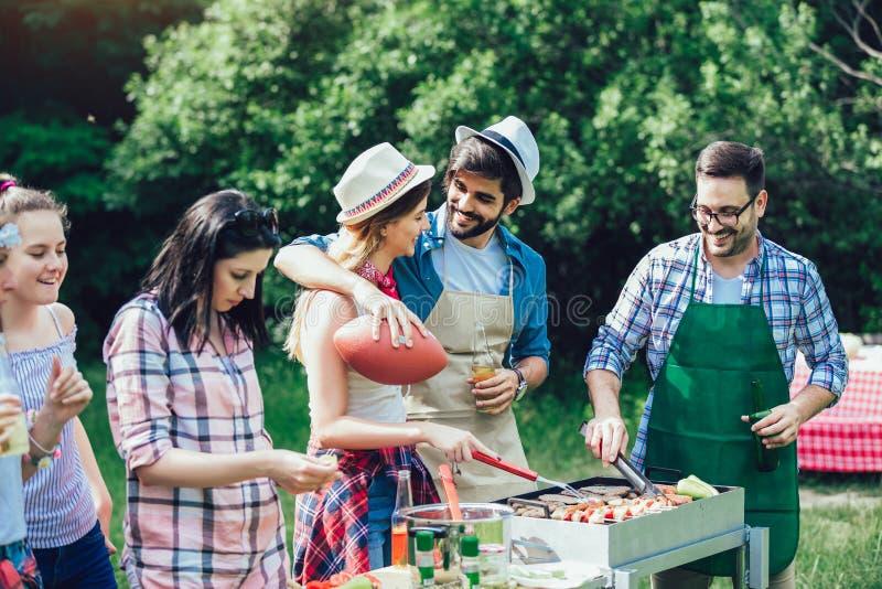Amis ayant l'amusement grillant la viande appréciant la partie de barbecue images stock
