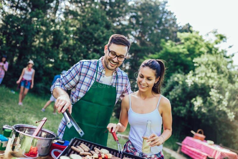Amis ayant l'amusement grillant la viande appréciant la partie de barbecue photographie stock