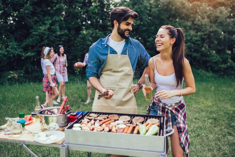 Amis ayant l'amusement grillant la viande appréciant la partie de barbecue image libre de droits