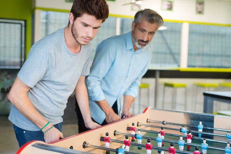 Amis ayant l'amusement jouant ensemble le football de table photos libres de droits