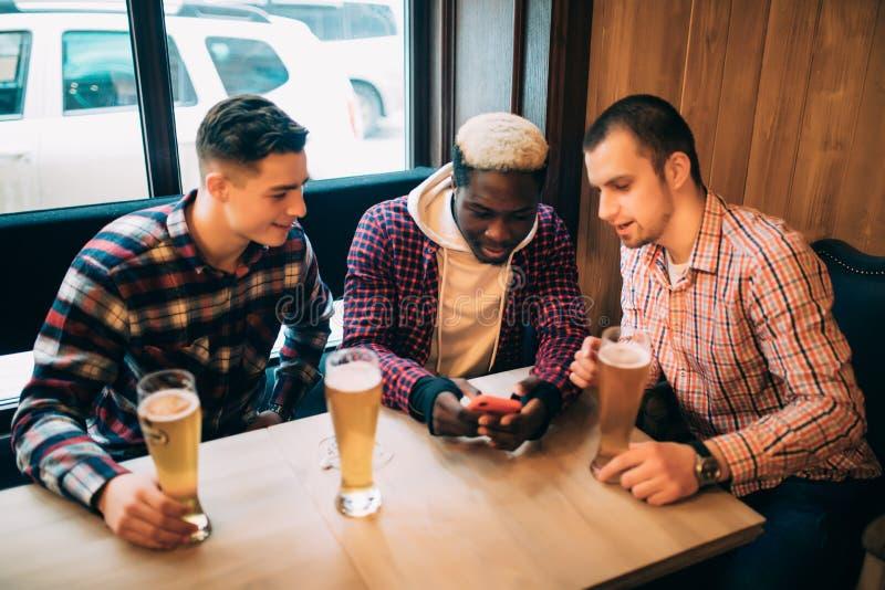 Amis ayant l'amusement Trois jeunes hommes heureux en bière potable de tenue de détente dans le bar tandis qu'un de regarder le t image stock