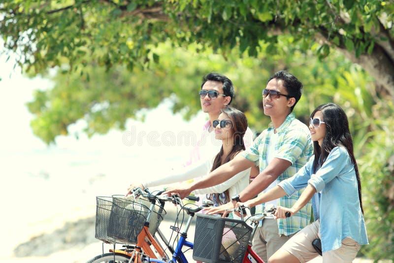 Amis ayant la bicyclette d'équitation d'amusement ensemble images stock
