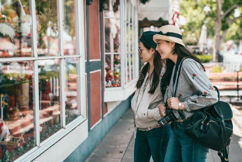 Amis ayant le lèche-vitrines dans la rue images libres de droits