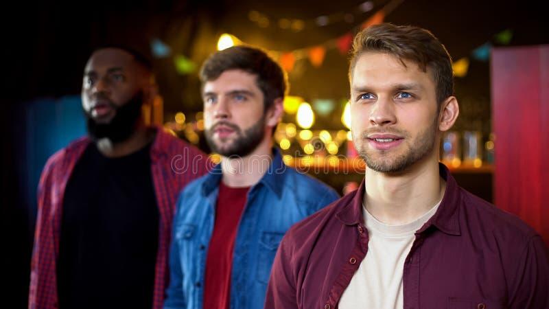 Amis beaux passant la soirée dans le club des hommes, célébrant l'enterrement de vie de jeune garçon image libre de droits