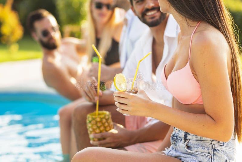 Amis buvant des cocktails par la piscine photo stock