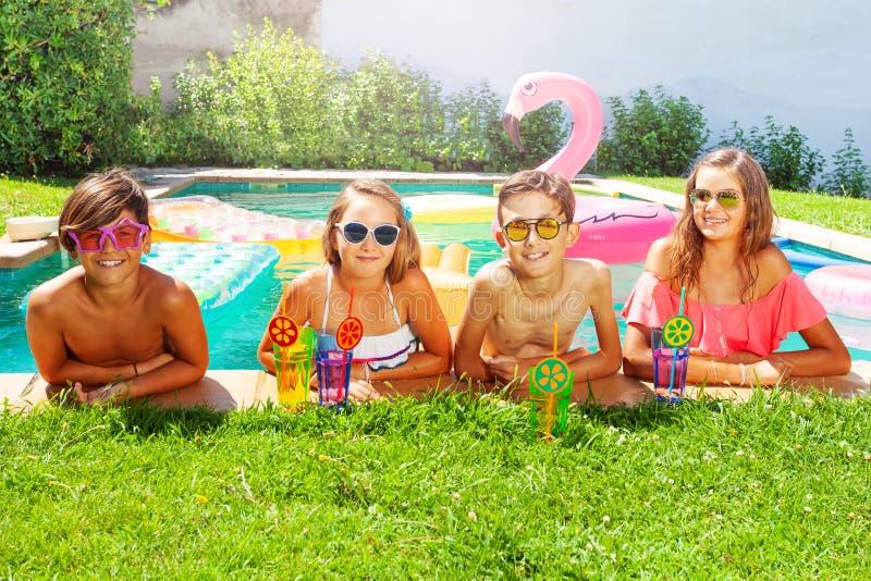 Amis buvant des cocktails pendant la réception au bord de la piscine photos libres de droits