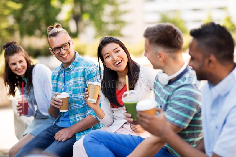 Amis buvant du café et du jus parlant dans la ville photo stock