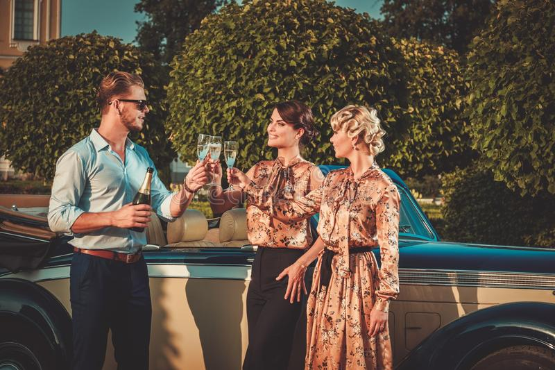 Amis buvant du champagne près de la voiture classique image libre de droits