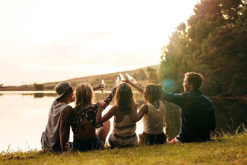 Amis célébrant avec des bières au lac images libres de droits