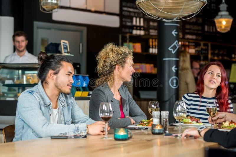 Amis conversant tout en ayant la nourriture au restaurant photos stock
