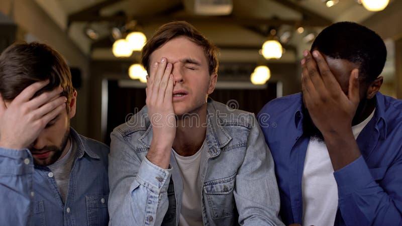Amis déçus fermant des visages avec le match de observation de main ensemble, mauvais résultat photographie stock