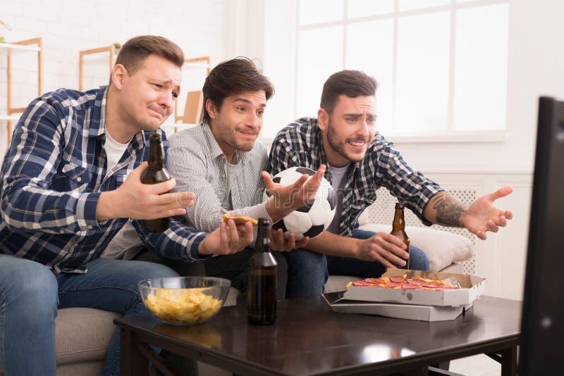 Amis déçus observant la maison d'Ay de match de football image stock