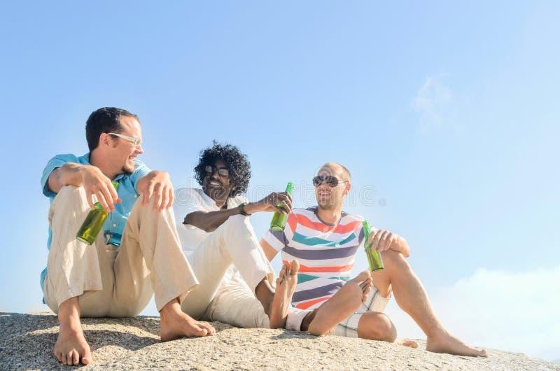 Amis détendant avec des bières un jour ensoleillé clair photo stock