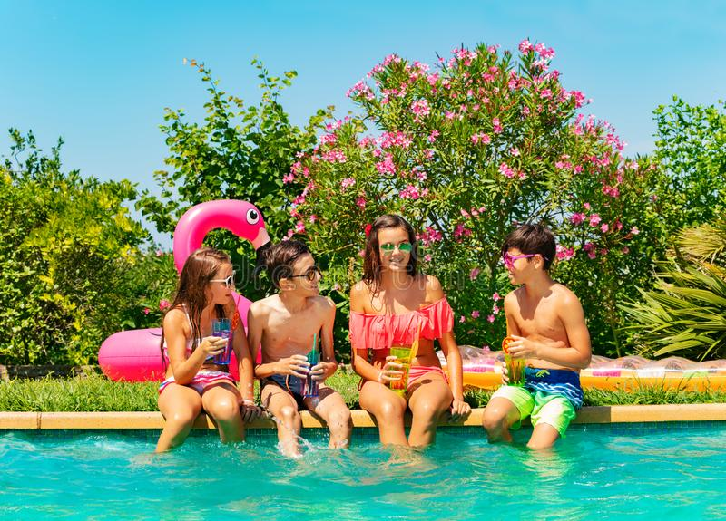 Amis détendant et ayant l'amusement pendant la réception au bord de la piscine image libre de droits